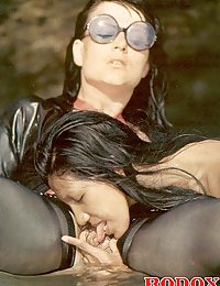 Kinky retro lesbians in latex having sex in the open air
